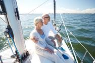 Senior couple hugging on sail boat or yacht in sea Stock Photos