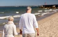 Senior couple walking along summer beach Stock Photos