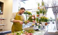 Smiling florist man making bunch at flower shop Stock Photos