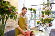 Florist wrapping flowers in paper at flower shop Stock Photos