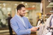 Happy young man choosing clothes in clothing store Stock Photos