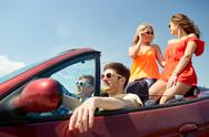 Happy friends driving in cabriolet car Stock Photos