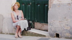 Female tourist sitting on a parade of old house door. Using cell phone Stock Footage