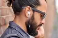 Close up of man with earphones listening to music Stock Photos