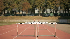 Two sprinters jumping over five hurdles on runways Stock Footage