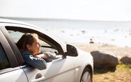 Happy teenage girl or young woman in car Stock Photos