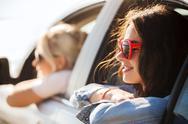 Happy teenage girls or women in car at seaside Stock Photos