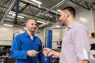 Auto mechanic giving key to man at car shop Stock Photos
