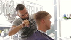 Barber scissors cuts the hair of the client Stock Footage