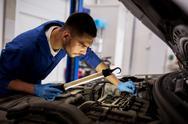 Mechanic man with lamp repairing car at workshop Stock Photos