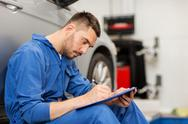 Auto mechanic man with clipboard at car workshop Stock Photos