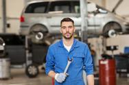 Auto mechanic or smith with wrench at car workshop Stock Photos