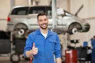 Happy auto mechanic man or smith at car workshop Stock Photos