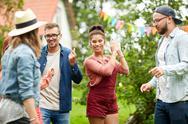 Happy friends dancing at summer party in garden Stock Photos