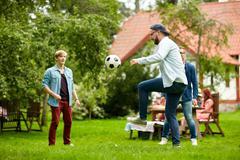 Happy friends playing football at summer garden Kuvituskuvat