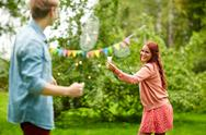 Happy friends playing badminton at summer garden Stock Photos