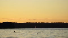 A small sailing boat on the water at sunset Stock Footage