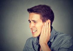 Tinnitus. Sick man having ear pain touching his painful head Kuvituskuvat