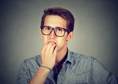Preoccupied anxious man biting fingernails nervously Stock Photos