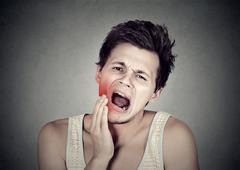 Man with toothache tooth pain outside mouth cheek colored in red Stock Photos