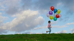 Young child runs across screen from left to right with balloons, in slow motion Stock Footage