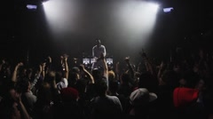 People raise hands jump on party in nightclub. Mc man performing on stage. Dance Stock Footage