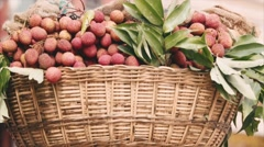 Green grocer carrying a basket of fruits lychee on his head. Closeup. Stock Footage