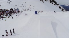 Quadrocopter shoot snowboarder ride on springboard. People in encamp. Mountains Stock Footage