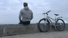 A lone man with bicycle sits on old high concrete pier during huge storm. Stock Footage