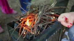Woman uses match to kindle branches in brazier for barbeque Stock Footage