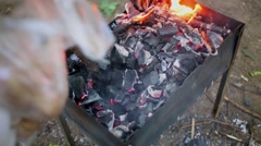 Stick turns charcoals in brazier before potato added inside for cooking Stock Footage