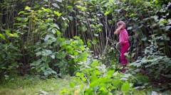 Young girl in pink clothes uses knife to cut branches with foliage Stock Footage