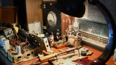 Work desk with obsolete tools and electronics devices under lamp light Stock Footage