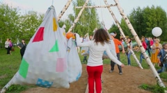 Woman runs by obstacle course with swaying bags near crowd of people Stock Footage