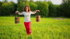 Woman carries shoulder-yoke by grass glade at summer sunny day Stock Footage