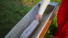 Woman beats wooden trough by mallet at summer day during fair Stock Footage
