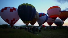 Group of air balloons inflated for fly on field with lot of people Stock Footage