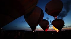 People watch preparation of air balloons with baskets during sunset Stock Footage