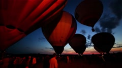 Fire burn in air balloons before fly on field with people Stock Footage