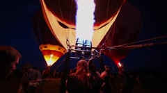 People sit in basket below fire which inflates air balloon Stock Footage