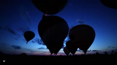 Fire inflates air balloons with baskets above field with people Stock Footage