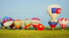 Eleven air balloons prepared for fly on grass field at sunny day Stock Footage