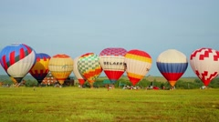 Colorful air balloons inflated before flight on grass field Stock Footage