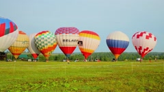 Grass field with eleven air balloons prepared for fly Stock Footage