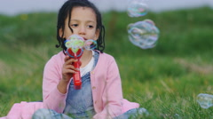 Little girl playing with a bubble gun outside on grass, in slow motion Stock Footage