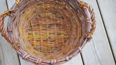 Handmade wattled basket with handles is on wooden floor Stock Footage