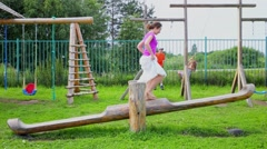 Mother and two her kids swing on playground at summer day Stock Footage
