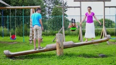 Four people family sway on playground at summer day Stock Footage
