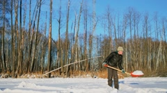 Young boy in warm clothes uses spade at sunny winter day Stock Footage