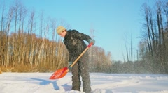 Young boy uses spade for lift and throw snow at sunny winter day Stock Footage